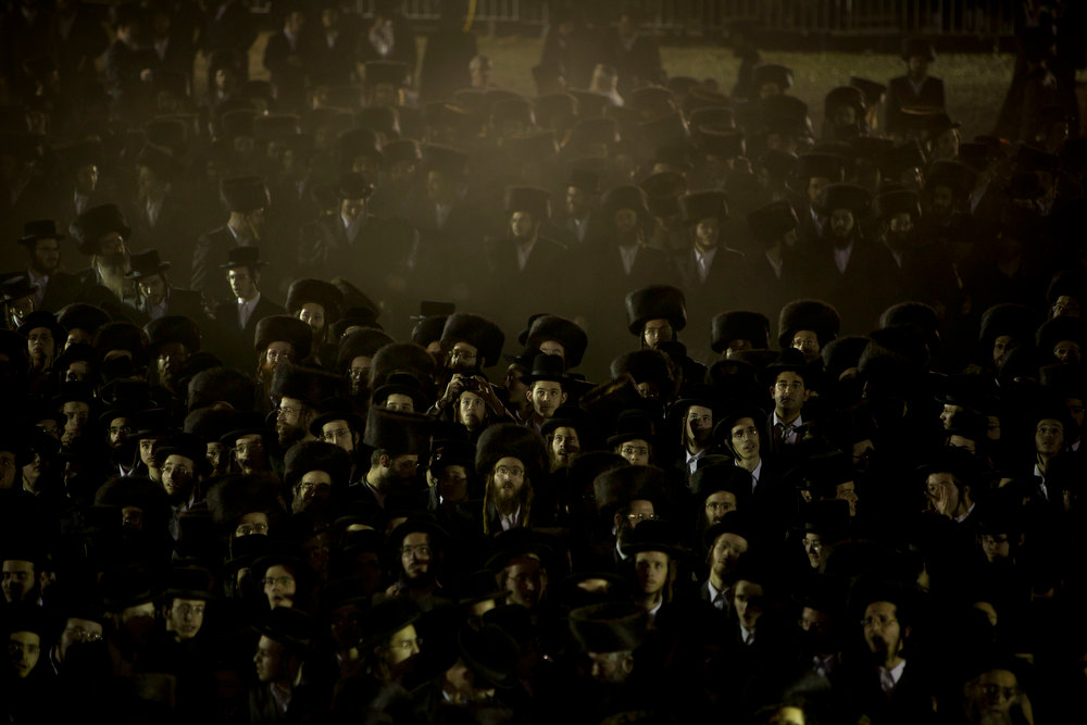 . Ultra-Orthodox Jews gather in the men\'s section for a traditional Jewish wedding of the great-grandson of the Rabbi of the Sanz Hasidic dynasty, in Netanya, Israel, Wednesday, Jan. 2, 2013. Thousands of people attended the wedding. (AP Photo/Oded Balilty)