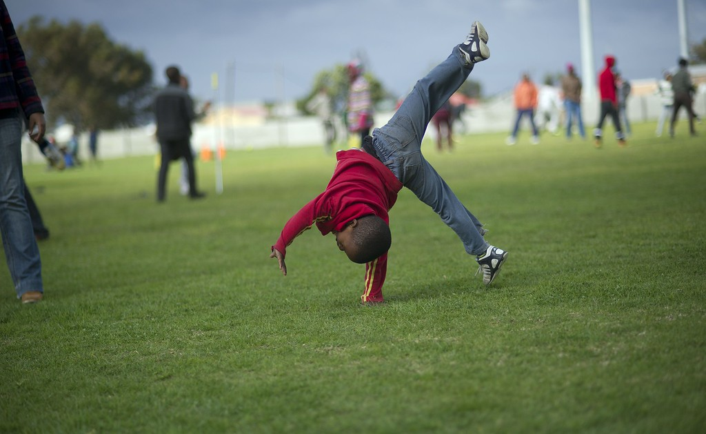 . A young boy does a cartwheel on a field, as sports and fun events are available, as part of the South African Rugby Union\'s and the City of Cape Town\'s contribution to Mandela Day, on July 18, 2014, in Langa, an impoverished area about 20Km from the centre of Cape Town. Mandela Day, celebrated on Nelson Mandela\'s birthday inspires people to give 67 minutes of their time, helping those less fortunate. 