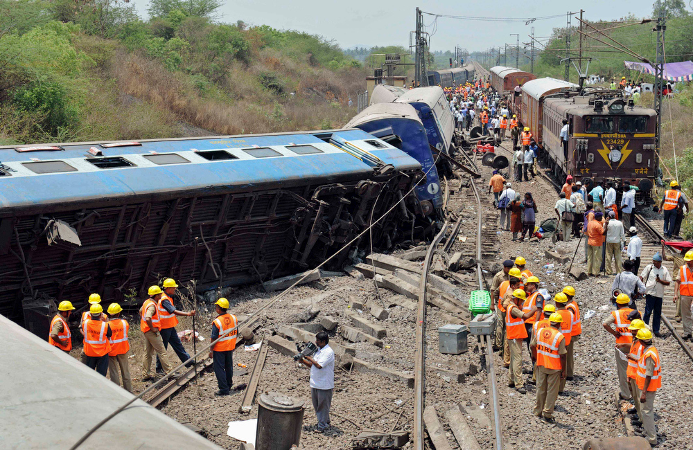 . Indian rescue workers gather at the site of a train accident near in Sitheri near Arakkonam, India, Wednesday, April 10, 2013. A passenger train traveling through southern Indian derailed at Sitheri, about 90 kilometers (56 miles) southwest of Chennai early Wednesday morning, killing one person and injuring dozens more, according to local reports. (AP Photo/Arun Sankar K.)