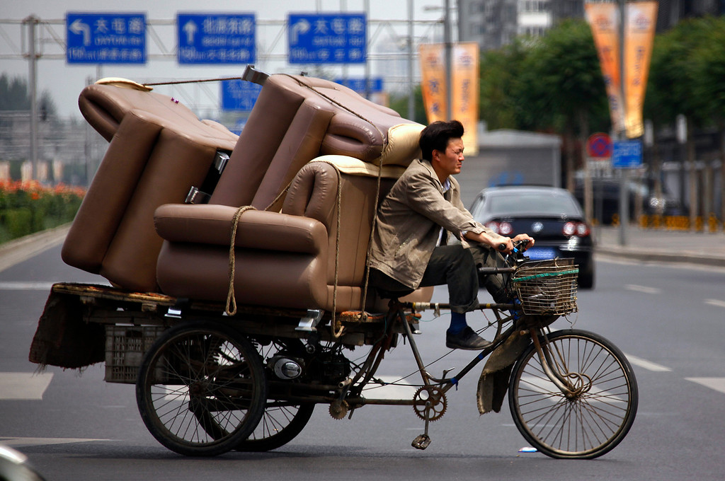 . A man rides a tricycle loaded with lounge chairs along a road in Beijing June 5, 2012.    REUTERS/David Gray