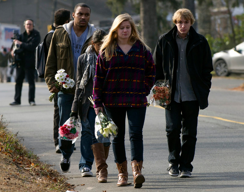 . Young people carry flowers to leave near Sandy Hook Elementary School on December 15, 2012 in Newtown, Connecticut. The residents of an idyllic Connecticut town were reeling in horror from the massacre of 20 small children and six adults in one of the worst school shootings in US history. The heavily armed gunman shot dead 18 children inside Sandy Hook Elementary School, said Connecticut State Police spokesman Lieutenant Paul Vance. Two more died of their wounds in hospital.   DON EMMERT/AFP/Getty Images