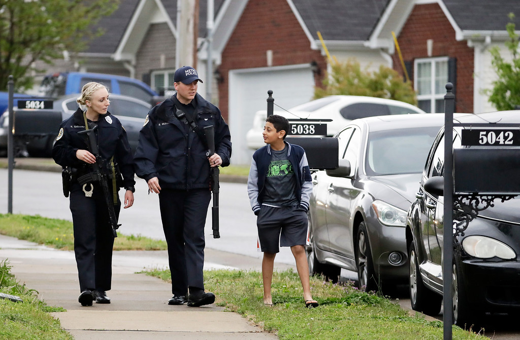 . Nashville police officers talk to a boy as they search a neighborhood near a Waffle House restaurant Sunday, April 22, 2018, in Nashville, Tenn. At least four people died after a gunman opened fire at the restaurant early Sunday. (AP Photo/Mark Humphrey)