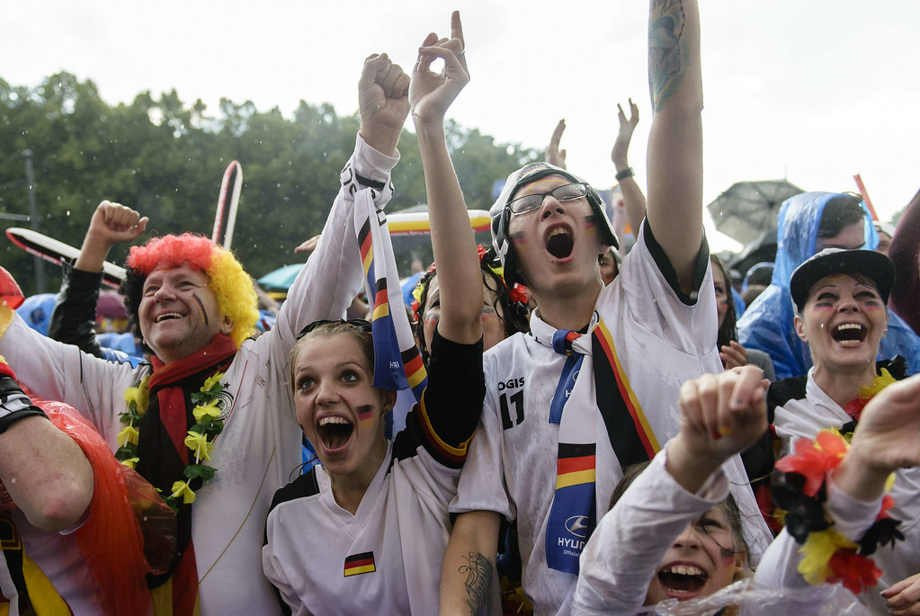 . German fans celebrate while they watch the FIFA World Cup 2014 group G football match Germany vs USA in the rain on a giant screen in Berlin, Germany on June 26, 2014. CLEMENS BILAN/AFP/Getty Images