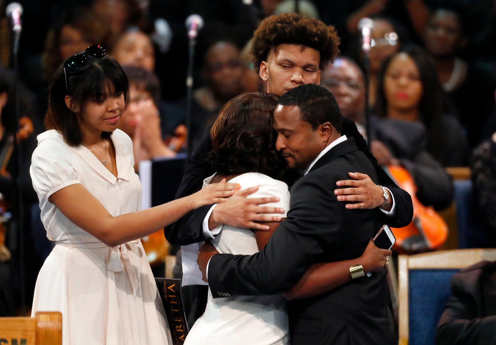 . Cristal Franklin, foreground left, hugs Vaughn Franklin as Victorie Franklin, left, and Jordan Franklin look on during the funeral service for Aretha Franklin at Greater Grace Temple, Friday, Aug. 31, 2018, in Detroit. Franklin died Aug. 16, 2018 of pancreatic cancer at the age of 76. (AP Photo/Paul Sancya)