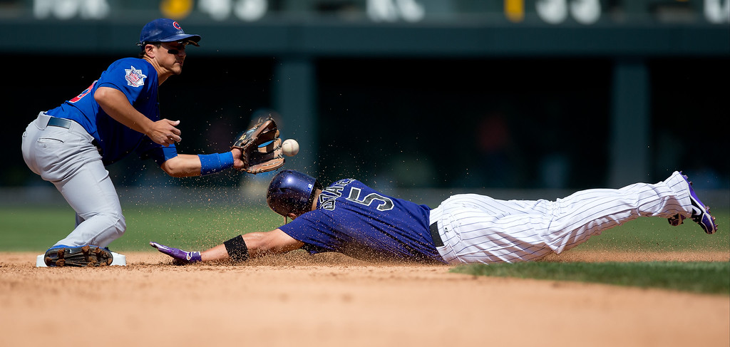 . Carlos Gonzalez #5 of the Colorado Rockies slides in safely for a stolen base before second baseman Darwin Barney #15 of the Chicago Cubs can receive the ball during the fourth inning at Coors Field on July 21, 2013 in Denver, Colorado. The Rockies defeated the Cubs 4-3.  (Photo by Justin Edmonds/Getty Images)
