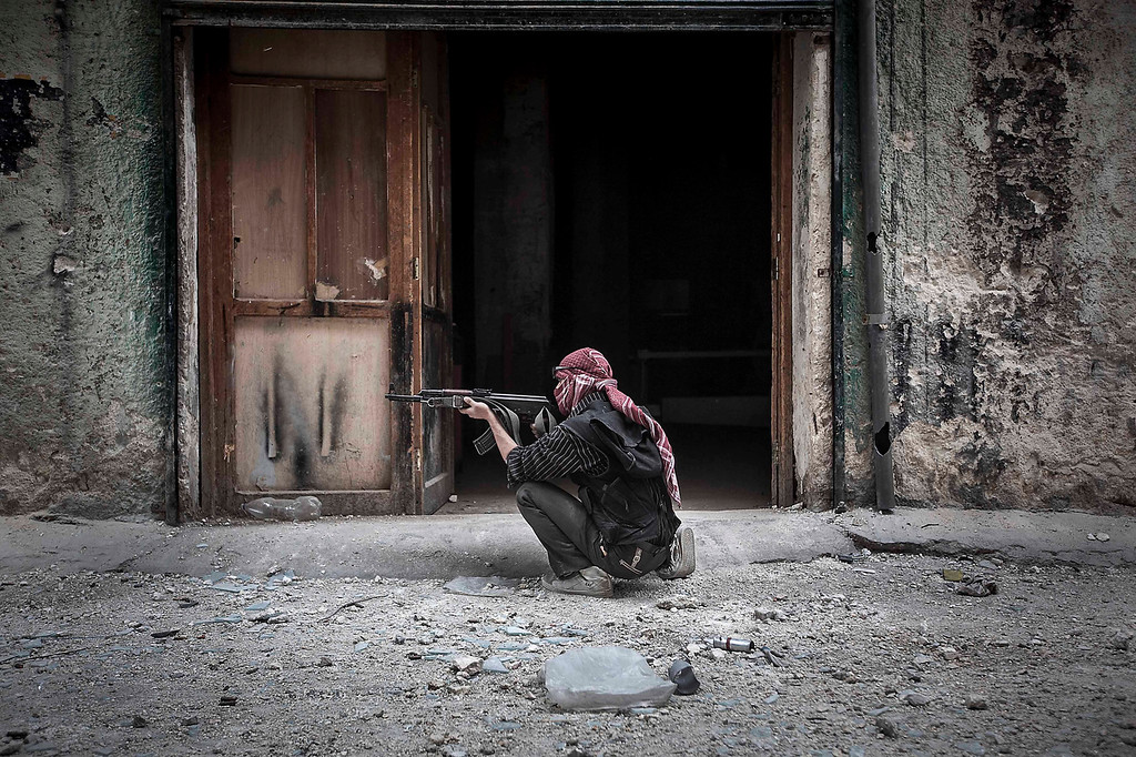 . In this Wednesday, Oct. 24, 2012 photo, a Free Syrian Army fighter sights a government  position as rebel fighters belonging to the Liwa Al Tawhid group carry out a military operation at the Moaskar front line, one of the battlefields in Karmal Jabl neighborhood, in Aleppo, Syria. (AP Photo/Narciso Contreras)