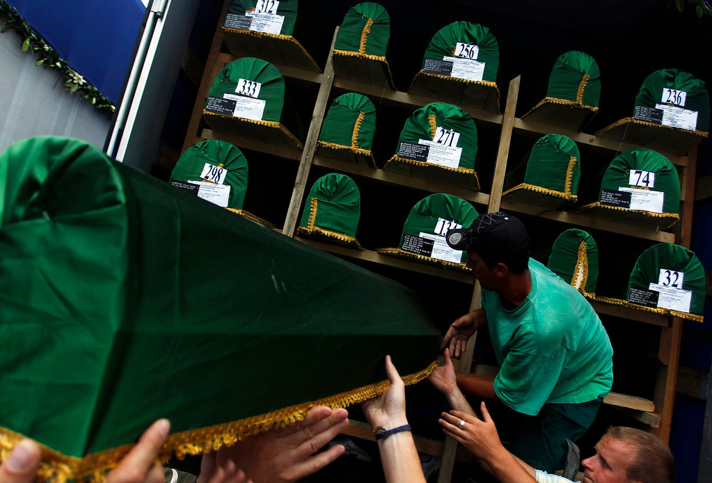 . Bosnian men unload coffins of the 409 newly identified victims of the 1995 Srebrenica massacre from a truck in Potocari Memorial Center, near Srebrenica July 9, 2013. The bodies of the recently identified victims will be buried on July 11 marking the 18th anniversary of the massacre in which Bosnian Serb forces commanded by Ratko Mladic killed up to 8,000 Muslim men and boys and buried them in mass graves. REUTERS/Dado Ruvic