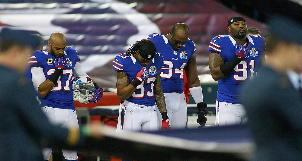 . Players from the Buffalo Bills observe a moment of silence for the victims of the mass shooting at Sandy Hook Elementary School in Newtown, Connecticut, before a game against the Seattle Seahawks at Rogers Centre on December 16, 2012 in Toronto, Ontario, Canada.  (Photo by Rick Stewart/Getty Images)