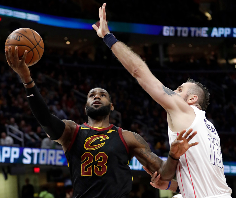 . Cleveland Cavaliers\' LeBron James (23) drives to the basket against Washington Wizards\' Marcin Gortat (13), from Poland, in the first half of an NBA basketball game, Thursday, April 5, 2018, in Cleveland. (AP Photo/Tony Dejak)