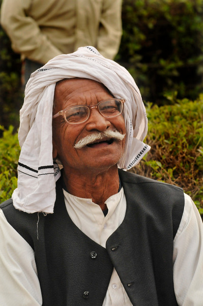 An elderly gentleman visiting the Gandhi raj ghat in Delhi with his family.