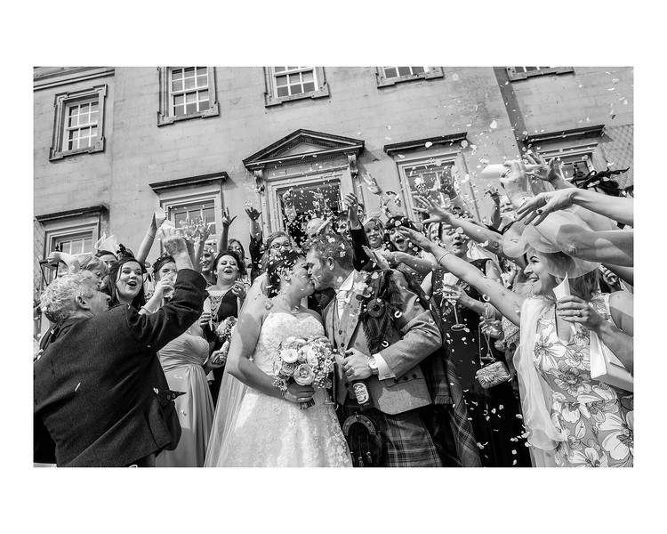 Wedding Photography of Louise & Jason, Dunfries House, Scotland, Photograph is of the Bride & Groom being covered in confetti