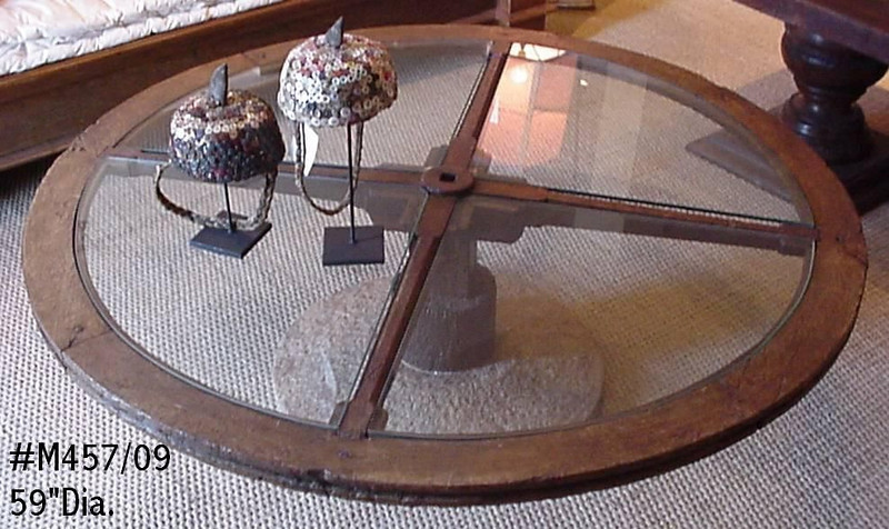 Antique wagon wheel mounted on mill wheel and made into a glass top coffee table