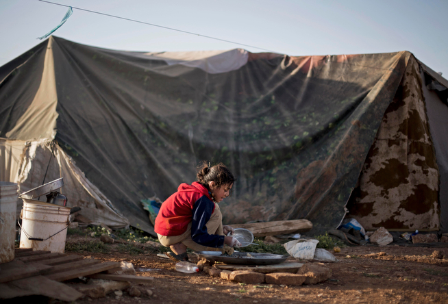 . In this Tuesday, April 8, 2014 photo, a Syrian refugee girl washes dishes in front of her family tent in an unofficial refugee camp on the outskirts of Amman, Jordan. Some residents, frustrated with Zaatari, the region\'s largest camp for Syrian refugees, set up new, informal camps on open lands, to escape tensions and get closer to possible job opportunities.(AP Photo/Khalil Hamra)