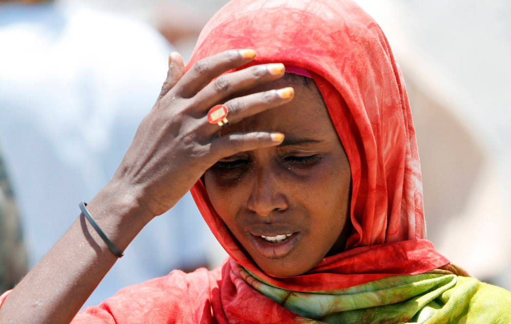 . A woman reacts as she walks past the scene of an explosion near the presidential palace in Somalia\'s capital Mogadishu, March 18, 2013. A car bomb exploded near the presidential palace in the Somali capital Mogadishu on Monday, killing at least 10 people in a blast that appeared to target senior government officials, police said. REUTERS/Feisal Omar