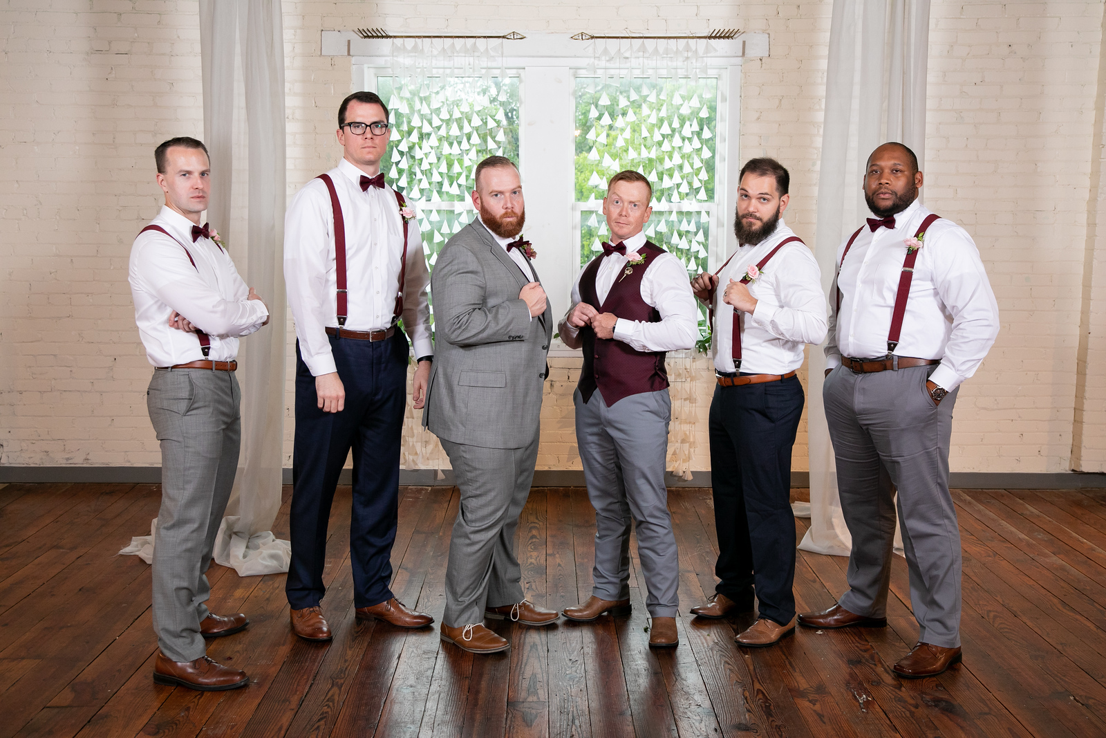five groomsmen wearing suspenders and non-matching shoes and slacks with burgundy bowties and pink boutonnieres