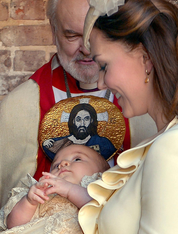 . Kate Duchess of Cambridge carries her son Prince George after his christening at the Chapel Royal in St James\'s Palace in London, with the Bishop of London Richard Chartres behind, Wednesday Oct. 23, 2013.  The prince was christened Wednesday with water from the River Jordan at a rare four-generation gathering of the royal family in London.  (AP Photo/John Stillwell, Pool)