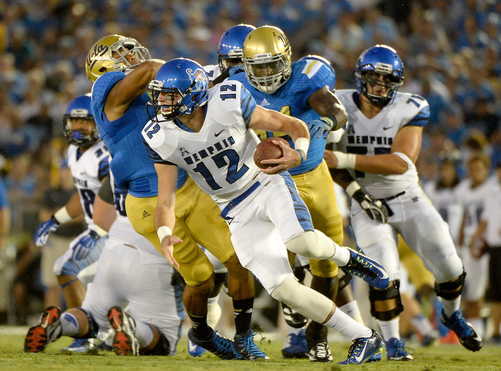 . PASADENA, CA - SEPTEMBER 06:  Memphis Tigers Paxton Lynch scrambles away from Aaron Wallace #51 and Owamagbe Odighizuwa #94 of the UCLA Bruins during the first half at Rose Bowl on September 6, 2014 in Pasadena, California.  (Photo by Harry How/Getty Images)