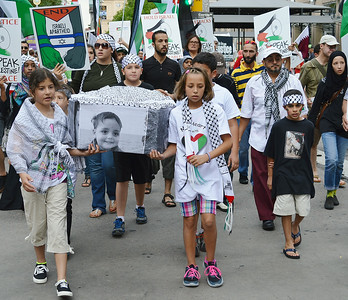 Young girls and boys carrying a mock coffin with photographs on side, some wearing keffiyehs, protest marchers with signs in background.
