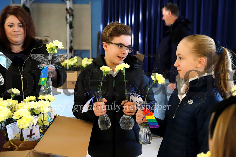 Jacob Hauser, 12, and Addison Johns, 11, prepare to deliver donated, leftover form Butler Catholic School's Purse Bash Fundraiser, for delivery to residents at area senior care facilities. Students from Butler Catholic made cards and helped deliver the left over flowers Saturday following the previous night's fundraiser. Seb Foltz/Butler Eagle (At St. Michael's parrish hall)