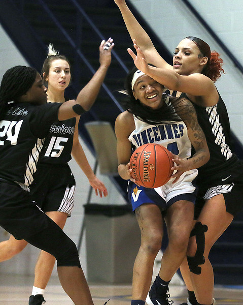 Photo by Matt Griffith/VU  Vincennes University's Jhala Henry, center, gets hit as she looks to shoot by Rend Lake's Dais'Ja Trotter, left,as the WarriorsNiy Danfort, 24, and Haleigh Keeling, 15, defend Saturday night in the P.E. Complex.