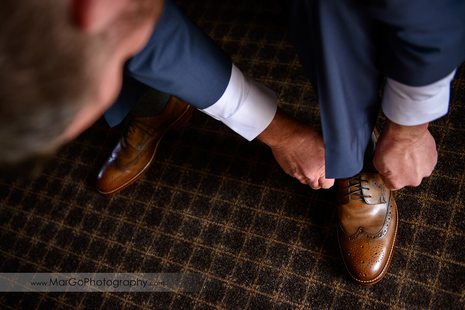 groom tying brown shoes during wedding preparation at Los Gatos Lodge