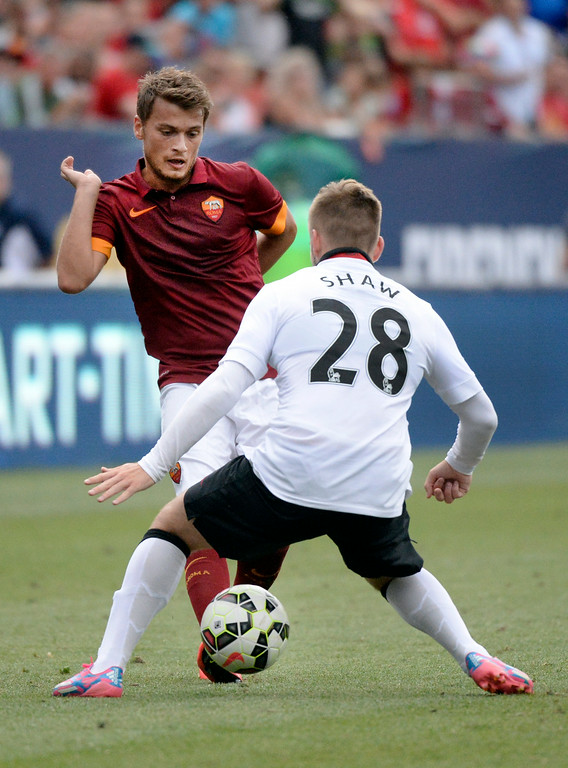 . AS Roma forward Adem Ljajic advanced the ball between the legs of Manchester United defender Luke Shaw in the second half. Manchester United defeated AS Roma 3-2 in an exhibition soccer game at Sports Authority Field in Denver Saturday afternoon, July 27, 2014. Photo by Karl Gehring/The Denver Post