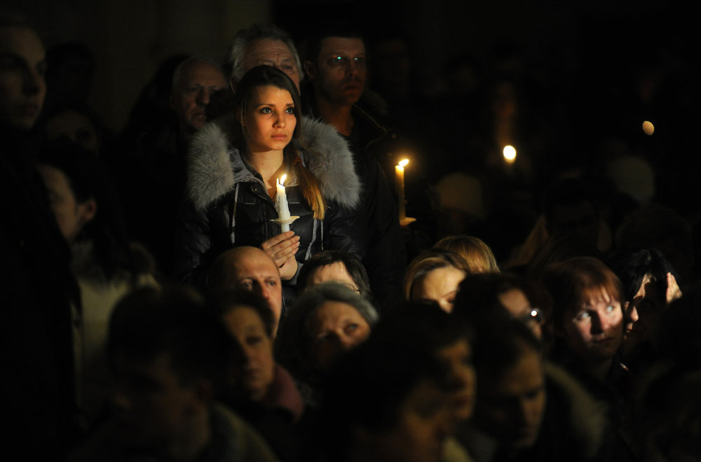 Description of . Russian Catholics hold candles during an Easter vigil on Holy Saturday at the Cathedral of Virgin Mary Immaculate Conception in Moscow on March 30, 2013.  Easter Vigil, also called the Paschal Vigil, is a service held in traditional Christian churches as the first official celebration of the resurrection of Jesus. While most Russians will mark Orthodox Easter on May 5, according to the old Julian calendar, Easter in the West is celebrated on March 30 by Russia's 600,000-strong Roman Catholic community.       AFP PHOTO / ANDREY SMIRNOV