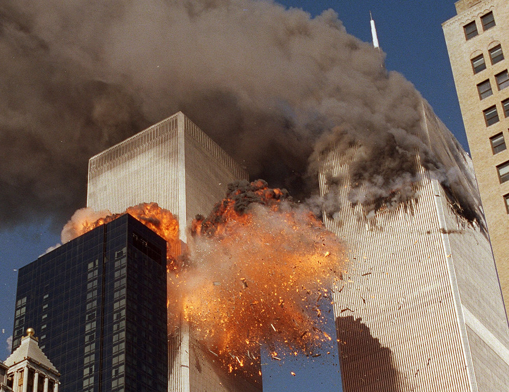 . Smoke billows from one of the towers of the World Trade Center and flames and debris explode from the second tower, Tuesday, Sept. 11, 2001. (AP Photo/Chao Soi Cheong)