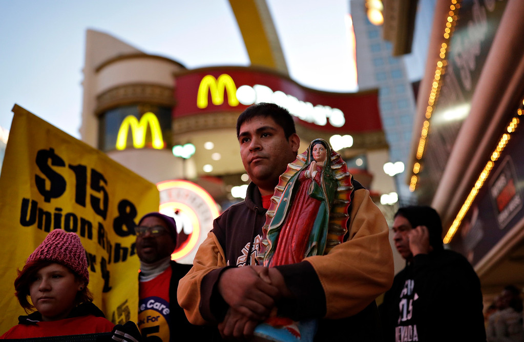 . Martin Macias-Rivera holds a statue as he and others protest near a McDonald\'s restaurant along the Las Vegas Strip, Tuesday, Nov. 29, 2016, in Las Vegas. The protest was part of the National Day of Action to Fight for $15. The campaign seeks higher hourly wages, including for workers at fast-food restaurants and airports. (AP Photo/John Locher)