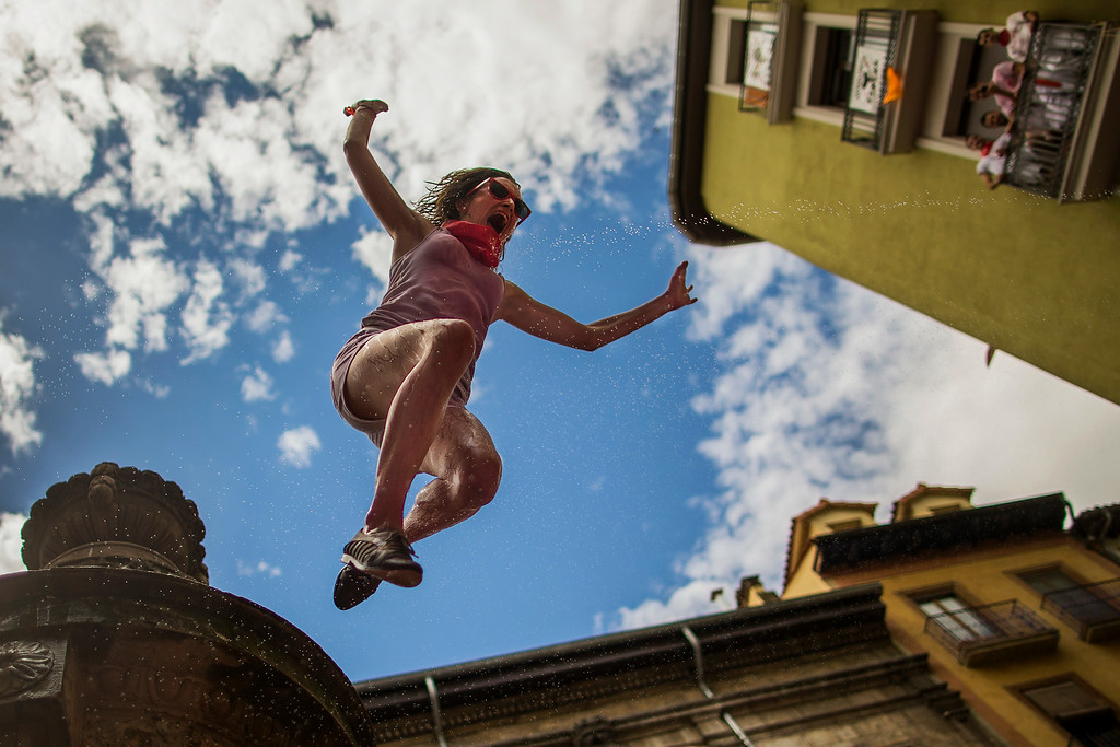 """. A reveler jumps from a fountain onto the crowd below, after the launch of the \'Chupinazo\' rocket, to celebrate the official opening of the 2014 San Fermin fiestas in Pamplona, Spain, Sunday, July 6, 2014. Revelers from around the world turned out here to kick off the festival with a messy party in the Pamplona town square, one day before the first of eight days of the running of the bulls glorified by Ernest Hemingway\'s 1926 novel \""""The Sun Also Rises.\"""" (AP Photo/Andres Kudacki)"""