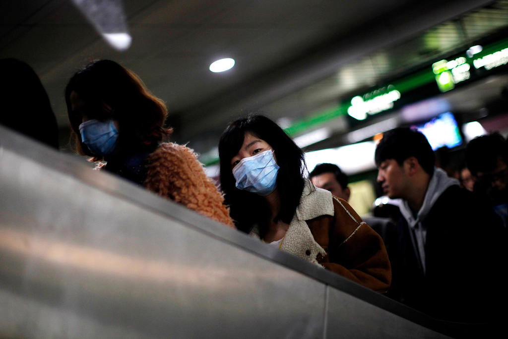 . A woman wears a face mask inside a subway station in Shanghai, April 5, 2013. Chinese authorities were slaughtering birds at a poultry market in the financial hub Shanghai as the death toll from a new strain of bird flu mounted to six on Friday, spreading concern overseas and sparking a sell-off on Hong Kong\'s share market. State news agency Xinhua said the Huhuai market for live birds in Shanghai had been shut down and birds were being culled after authorities detected the H7N9 virus from samples of pigeons in the market. All of the 14 reported infections from the H7N9 bird flu strain have been in eastern China and at least four of the dead are in Shanghai, a city of 23 million people and the showpiece of China\'s vibrant economy. REUTERS/Carlos Barria