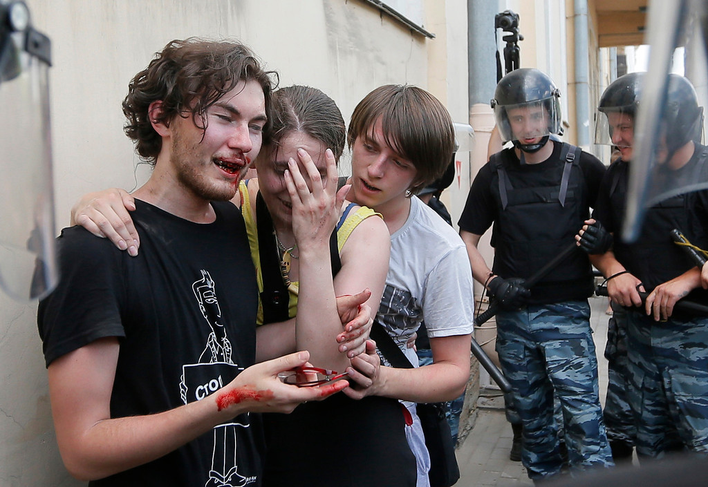 . Riot police (OMON) guard gay rights activists who have been beaten by anti-gay protesters during an authorized gay rights rally in St.Petersburg, Russia, Saturday, June 29, 2013.  Police detained several gay activists, who were outnumbered by the protesters. Dozens of gay activists had to be protected by police as they gathered for the parade, which proceeded with official approval despite recently passed legislation targeting gays. (AP Photo/Dmitry Lovetsky)