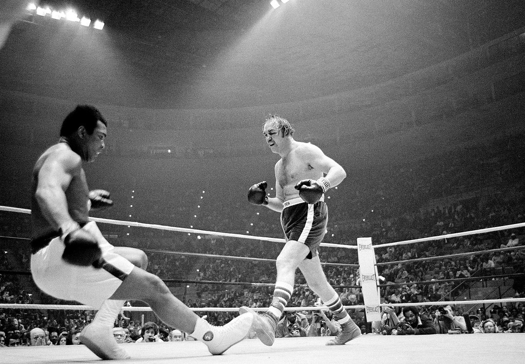 . Defending heavyweight champion Muhammad Ali goes down in the ninth round of the title bout against challenger Chuck Wepner, from Bayonne, N.J., at the Richfield Coliseum, in Cleveland, Ohio, on March 24, 1975. Ali tripped over Wepner\'s foot, but the referee ruled it as a knockdown. Ali later knocked out Wepner in the 15th round to retain his title. (AP Photo)
