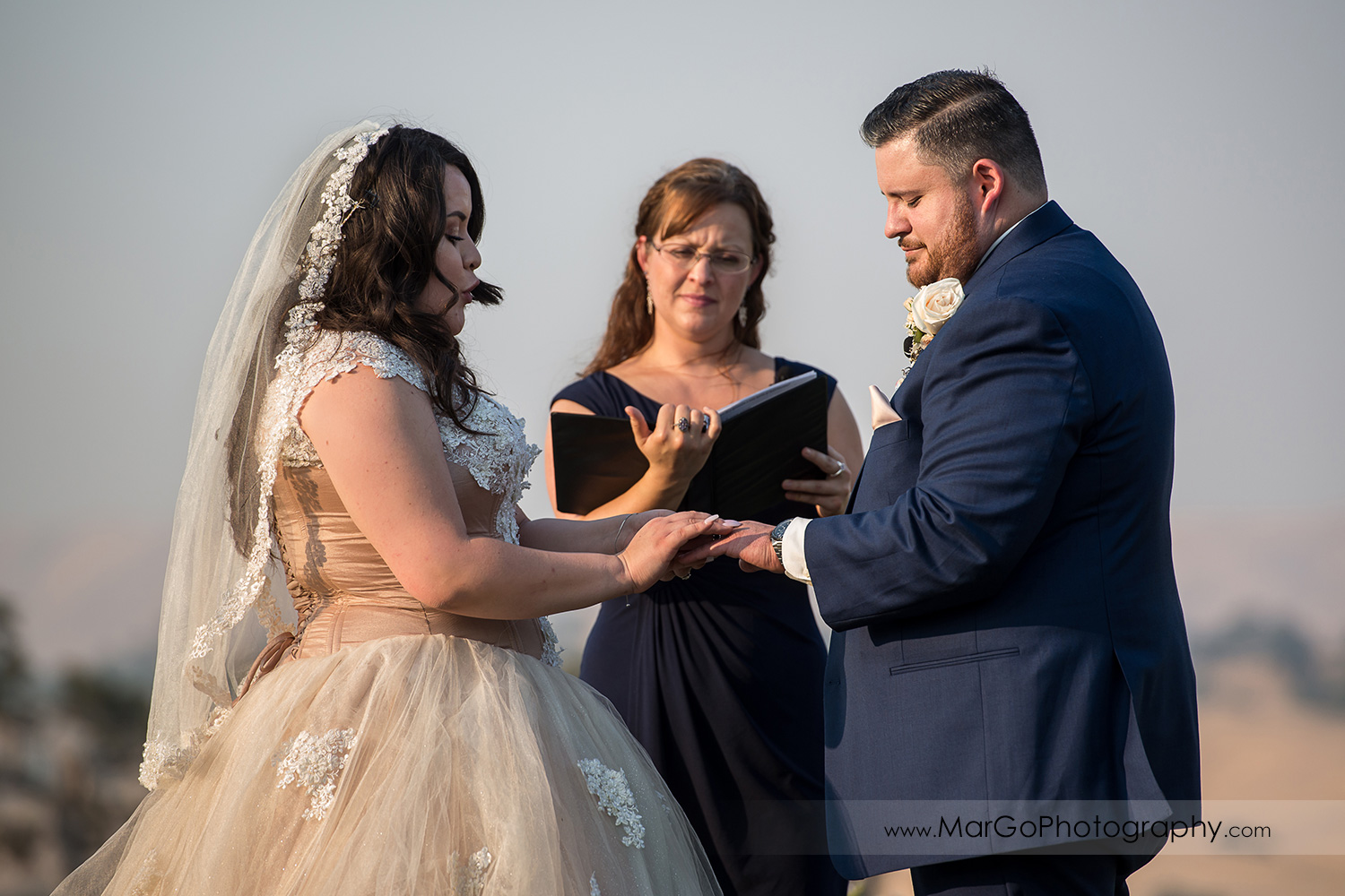 bride putting ring on groom's finger during wedding ceremony at Taber Ranch Vineyards