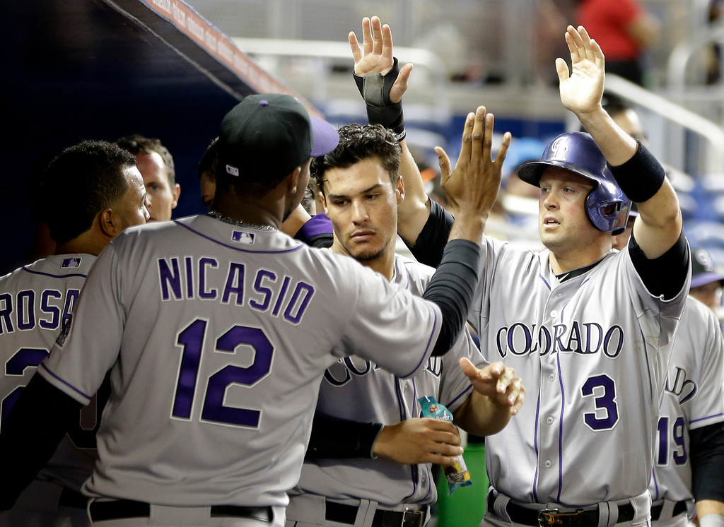 . Colorado Rockies\' Michael Cuddyer (3) is congratulated in the dugout after scoring on a double by Carlos Gonzalez in the eighth inning of a baseball game, Tuesday, April 1, 2014, in Miami. The Marlins defeated the Rockies 4-3. (AP Photo/Lynne Sladky)