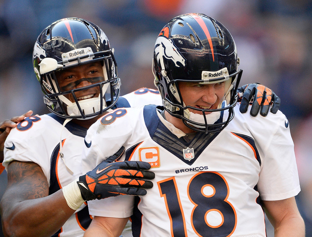 . Denver Broncos quarterback Peyton Manning (18) is congratulated by Denver Broncos wide receiver Demaryius Thomas (88)  after throwing his 51st touchdown pass of the season to Denver Broncos tight end Julius Thomas (80) late in the fourth quarter against the Houston Texans December 22, 2013 at Reliant Stadium. Manning passes Tom Brady for the most touchdown passes in a single season. (Photo by John Leyba/The Denver Post)