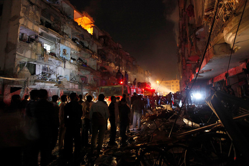 . Residents and firefighters gather at the site after a bomb blast in a residential area in Karachi March 3, 2013. A bomb attack in a Shi\'ite Muslim area of Pakistan\'s commercial capital Karachi killed 25 people and wounded 50 on Sunday, the police said. REUTERS/Akhtar Soomro