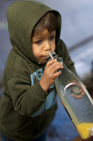 Little Aboriginal boy drinking orange juice from bottle