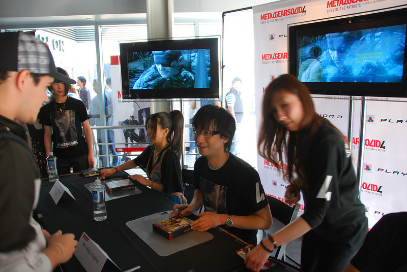 Mr. Kojima, famed creator of the 20-year spanning Metal Gear series, autographs a copy of MGS4 alongside the lovely Yumi Kikuchi, fashion model and MGS4 'Raging Raven' voice and motion capture actress...