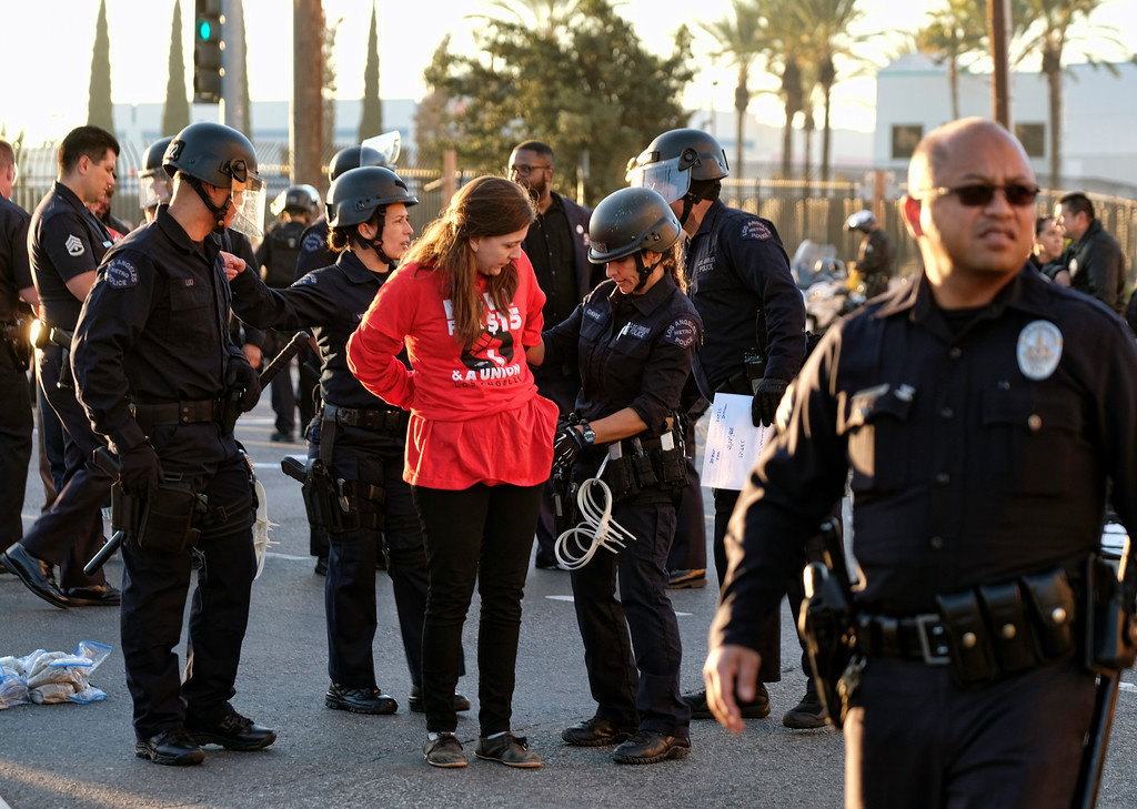 ". A protester is arrested and taken into custody during a wage protest in downtown Los Angeles on Tuesday, Nov. 29, 2016. A few dozen protesters blocked a downtown Los Angeles intersection as part of a national wave of demonstrations in support of higher wages and workers\' rights. Police stood by as the peaceful demonstrators formed a circle in the street early Tuesday while hoisting signs saying ""the whole world is watching\"" and \""Fight for $15.\"" (AP Photo/Richard Vogel)"