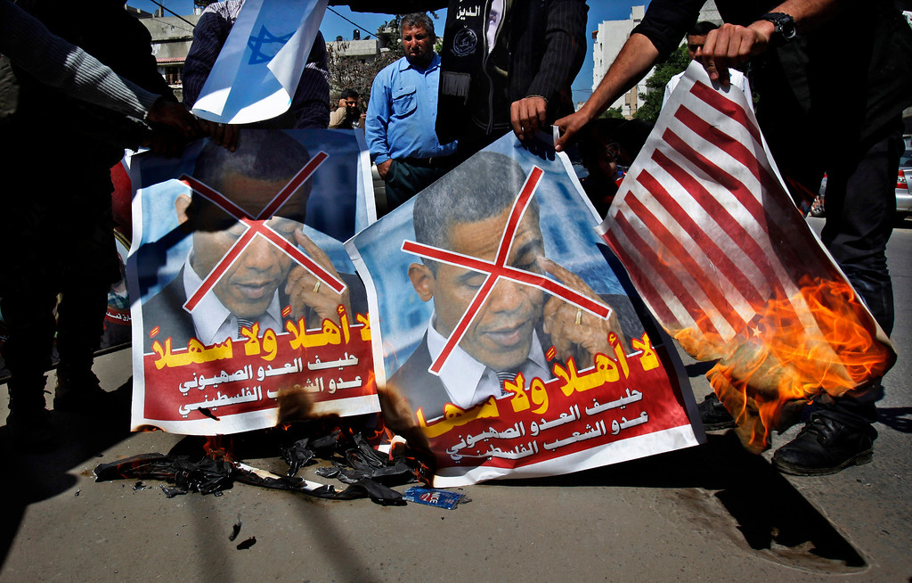 ". Palestinians burn posters of U.S. President Barack Obama and American flags during a protest against Obama\'s visit to the West Bank in Gaza City, Thursday, March 21, 2013. Arabic on posters read, ""you are unwelcome, the ally of the Zionist enemy and the enemy of the Palestinian people.\"" Obama is meeting Palestinian officials on the second day of his Mideast tour to emphasize the importance of reaching an Israeli-Palestinian peace deal. (AP Photo/Adel Hana)"