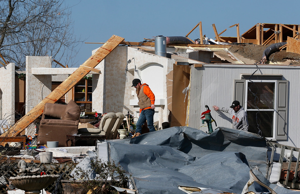 . Oklahoma Natural Gas workers walk through the tornado-damaged River Oaks Estates mobile home park in Sand Springs, Okla., Thursday, March 26, 2015. Gov. Mary Fallin has declared a state of emergency for 25 Oklahoma counties after powerful storms rumbled across the state Wednesday evening and produced tornadoes and flat-line winds that led to one death, numerous injuries and widespread damage. (AP Photo/Sue Ogrocki)