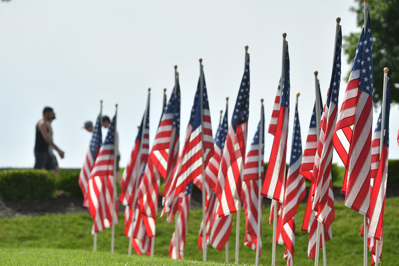 Visitors to the World War I Museum and Memorial walk past the 140 flags placed in the south lawn. Each of the 140 flags represents a veteran lost to suicide in one week. May 26, 2021