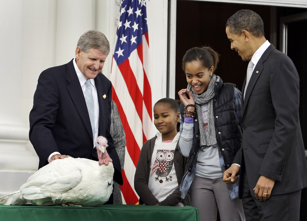 . President Barack Obama, right, with daughters, Sasha Obama, 8, Malia Obama, 11, reacts with Walter Pelletier, chairman of the National Turkey Federation, as Malia reaches to pet a turkey, Courage, the day before Thanksgiving, during a ceremony in the North Portico of the White House in Washington Wednesday, Nov. 25, 2009.(AP Photo/Alex Brandon)