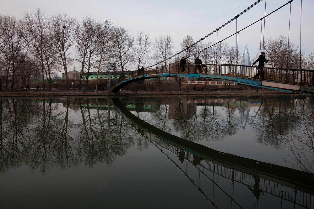 . North Koreans use a pedestrian bridge to cross over the Pothong River in Pyongyang on Sunday, Feb. 12, 2012.  (AP Photo/David Guttenfelder)