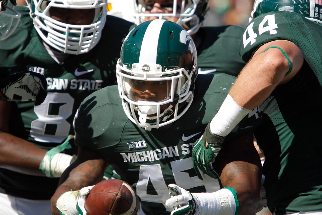 . Michigan State\'s Darien Harris, center, Shilique Calhoun, left, and Marcus Rush (44) celebrate Harris\' fumble recovery against Wyoming during the first quarter of an NCAA college football game, Saturday, Sept. 27, 2014, in East Lansing, Mich. Michigan State won 56-14. (AP Photo/Al Goldis)