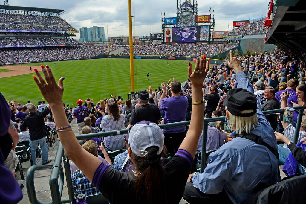 . Fans celebrate after Wilin Rosario (20) of the Colorado Rockies hits a home run in the fourth inning. (Photo by Andy Cross/The Denver Post)