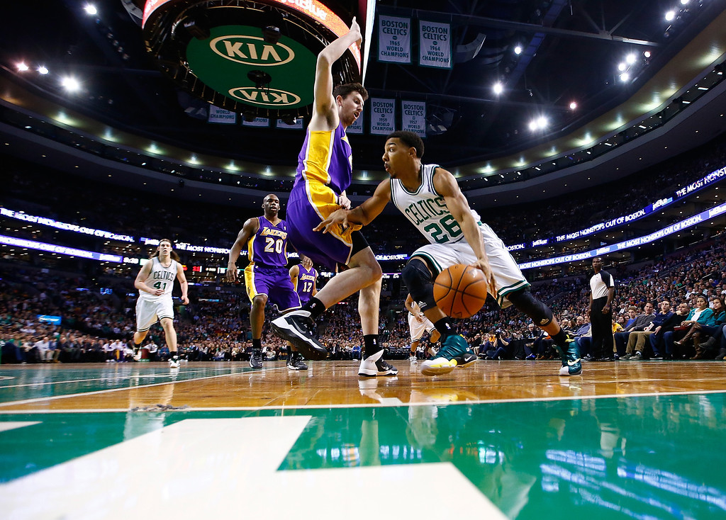 . BOSTON, MA - JANUARY 17: Phil Pressey #26 of the Boston Celtics drives the baseline past Ryan Kelly #4 of the Los Angeles Lakers in the second quarter during the game at TD Garden on January 17, 2014 in Boston, Massachusetts.   (Photo by Jared Wickerham/Getty Images)