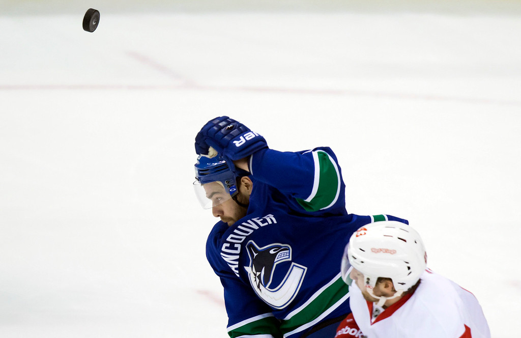 . Vancouver Canucks\' Chris Higgins, left, is checked by Detroit Red Wings\' Darren Helm as he reaches for the puck during the second period of an NHL hockey game in Vancouver, British Columbia on Saturday, Jan. 3, 2015. (AP Photo/The Canadian Press, Darryl Dyck)