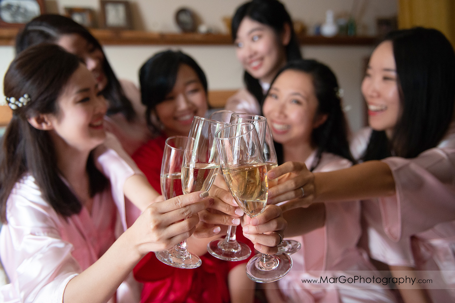 bride in red robe and bridesmaids in pink robes raising champagne glasses at Long Branch Saloon & Farms in Half Moon Bay